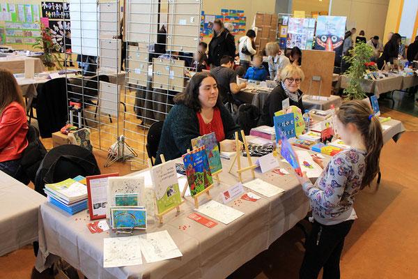 Une jeune lectrice de Zip le lutin avec l'illustratrice Cloé Perrotin au Salon du Livre Les petites pages Châtillonnaises 2018