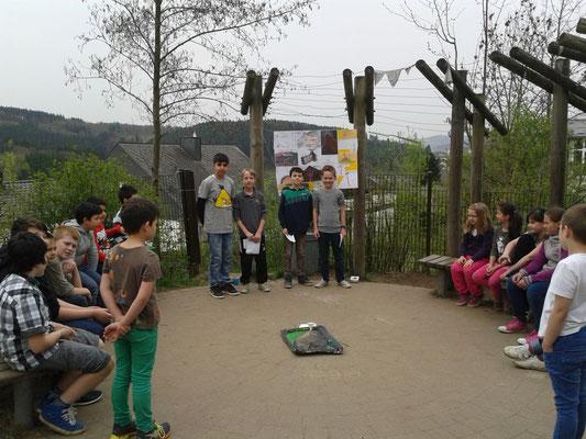 Hier halten vier Kinder einen Vortrag über Vulkane. Dazu haben sie ein Modell gebaut und ein Lernplakat erstellt.