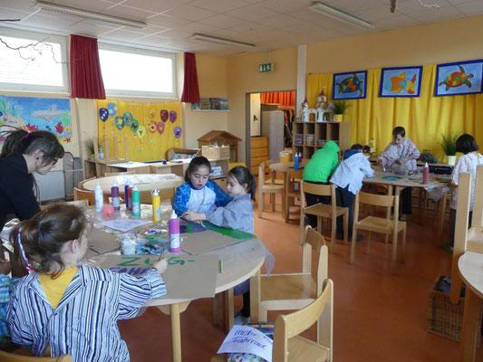Hier sieht man Kinder aus der Piratenklasse, die voll Begeisterung Plakate malen.