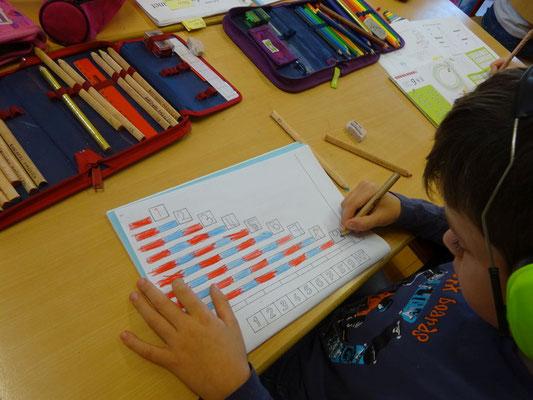 Nachdem mit den blau-roten Stangen gearbeitet wurde, wird nun das Wissen im Heft angewendet.