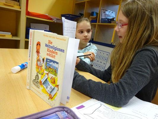 Einen Bereich, den die Kinder besonders lieben, ist das Erarbeiten von selbst gewählten Themen. Diese Mädchen wollen ein Lernplakat zu den Weltreligionen erarbeiten.