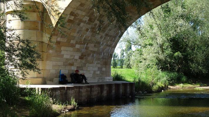 Philippe sous une pile de pont en attendant le train