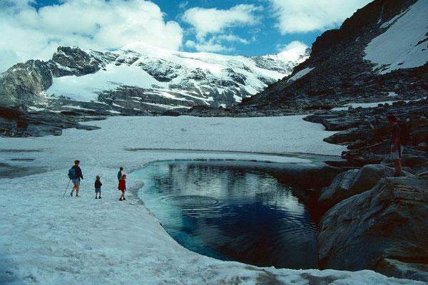 Kleine, noch halb zugefrorene Seelein (Medelzlacke) oberhalb der Bergstation des Medelzkopflifts. Im Hintergrund Johannisberg, 3453 m.