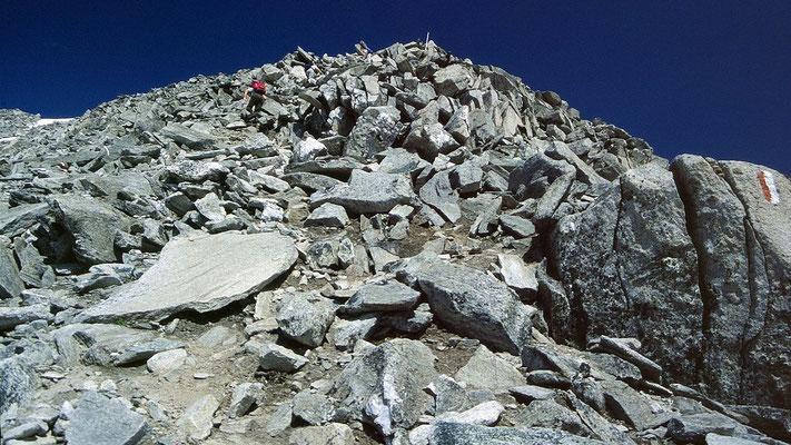 Foto beim Abstieg: Schlussanstieg und leichte Kletterei eines aufsteigenden Bergsteigers über den steilen Blockrücken zum Keeskogelgipfel