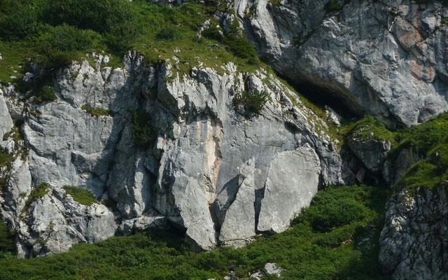 Drei zusammengehördene Teil einer großen geborstenen Felsplatte im rechten Seitenhang auf dem Weg zur Bushaltestelle