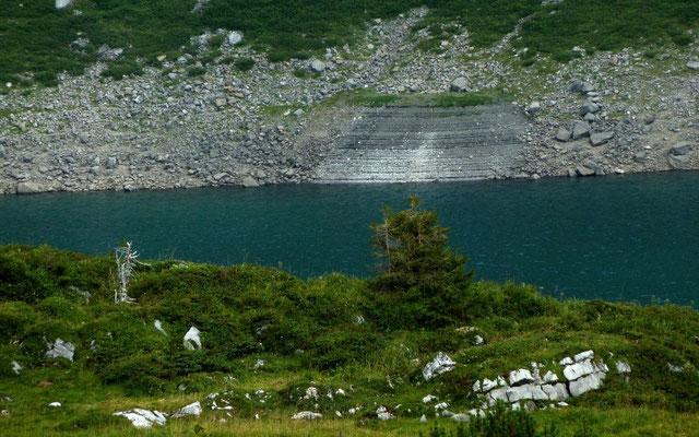 Freigelegte Felsschichten, an denen sich der Wasserstand des Formarinsees, der über keinen oberirdischen Abfluss verfügt, ablesen lässt.