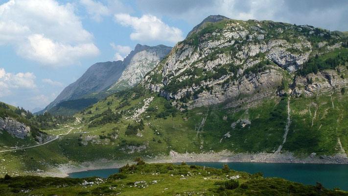 Unterhalb der Felsbänder in der östlichen Bergflanke hinter dem See verläuft der Felsensteig zur Freiburger Hütte