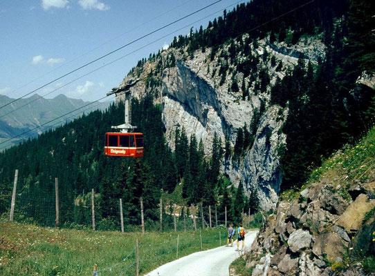 Die Elsigenalpbahn. Die Fortsetzung des Wanderwegs nach Frutigen führt und ihr durch und an der hinteren Felswand, einem Klettergarten, vorbei.