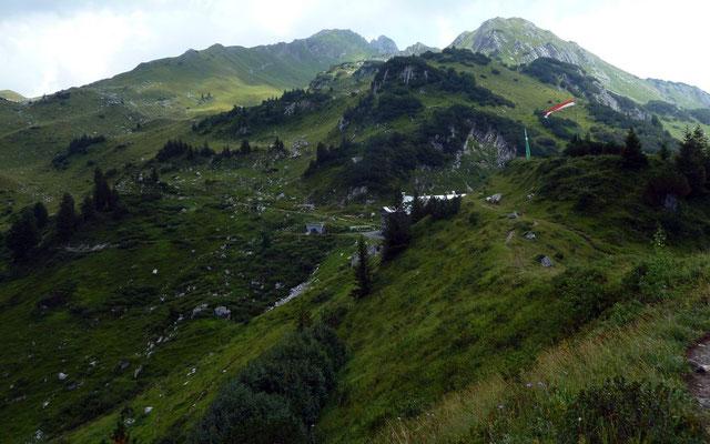 Die kleine Anhöhe mit Fahnenmasten und die Hütte vom Güterweg zur Formarinalpe. In der Bildmitte oben spitzt die Roggalspitze hinten hervor.