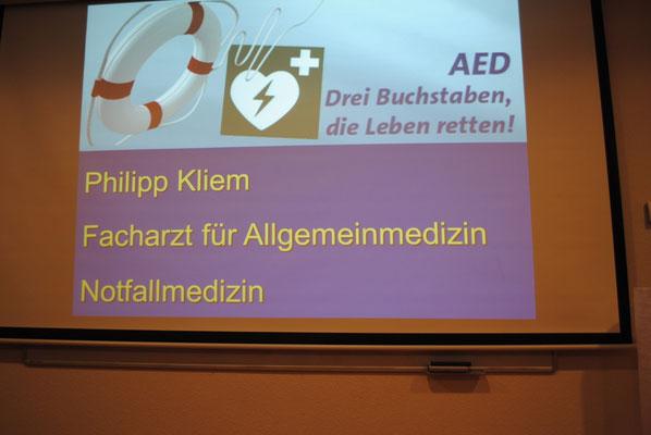 Mit diesem Zeichen und den Großbuchstaben AED sind die derzeit in vielen öffentlichen Gebäuden aufgehängten Defibrilatoren gekennzeichnet und weithin gut sichtbar, so dass sie im Notfall Leben retten können.