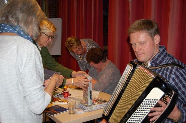 Andrang am Büchertisch - beim Signieren der Bücher wurde Renate Kiekebusch durch Akkordeonspieler Thomas Sölter begleitet