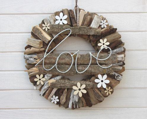 Holzblumen und der Metallschriftzug sind die Blickpunkte des Holzkranzes.