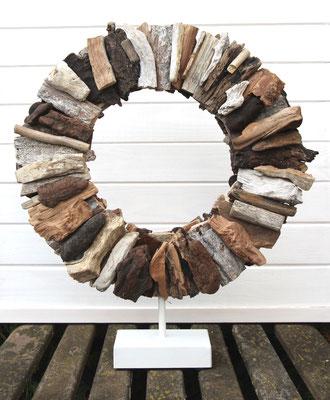 Braun - weißer Treibholzkranz auf cremeweißem Metallsockel.