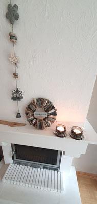 Graue Girlande zusammen mit einem Treibholzkranz dekoriert.