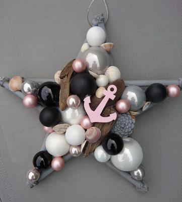 Maritim gestalteter Dekostern aus schwarzen und weißen Glaskugeln, braunem Treibholz und rosafarbenem Anker.