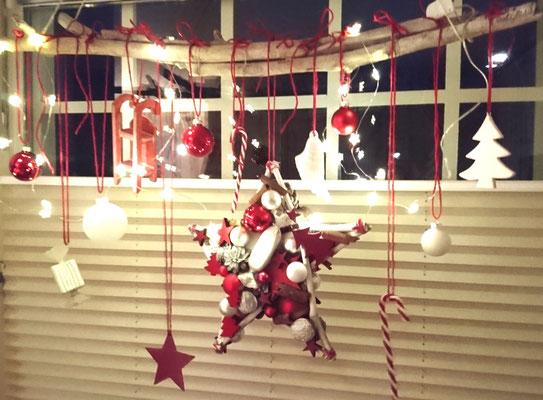 Hängende Adventsdekoration aus einem handgefertigtem Stern, weißen und roten Accessoires an Treibholzästen mit Microlichterkette beleuchtet.