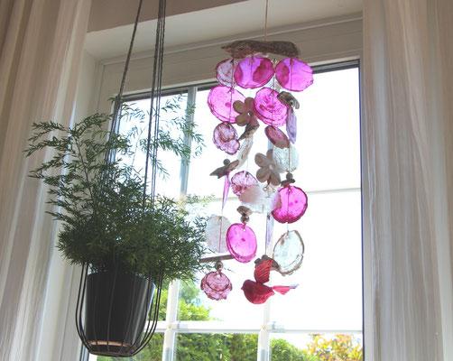 Windspiel im Fenster, neben einer Blumenampel dekoriert.
