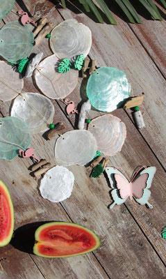 Windspiel mit Holzflamingos und grünen tropischen Blättern, kombiniert mit einer Wassermelone.