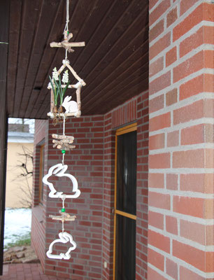 Weiße Girlande mit Osterhasen an der Terrasse aufgehängt.