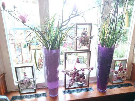 Fensterdekoration mit violetten Glasvasen, weihnachtliche Sterne an receycelte Holzrahmen gehängt.