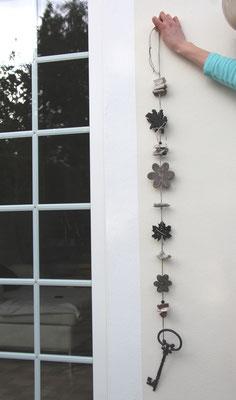 Girlande mit schwarzem Schlüssel und grauen Holz Blüten.