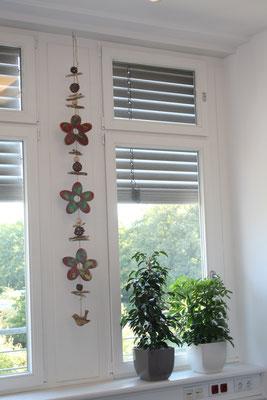 In einer Praxis zwischen zwei großen Fenstern - eine Dekokette mit Holzblumen und Holzvögeln.