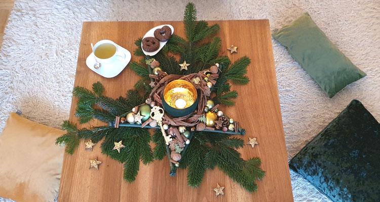 Gemütliches Teestunde mit Tischstern - grünen Tannenzweigen und Lebkuchen auf einen braunen Tisch dekoriert.