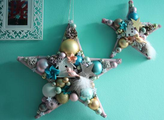 Zwei Sterne in zwei Größen an einer türkisfarbenen Wand mit Vögeln in gold und Pastellfarben.