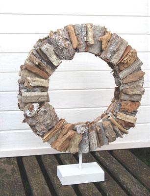 Nachhaltige Naturdekoration aus Treibhölzern auf cremeweißem Metallsockel.