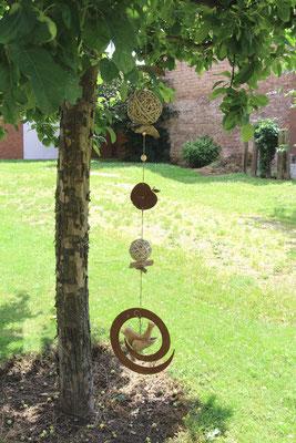 Edelrost Metallgirlande am Apfelbaum als Gartenschmuck.