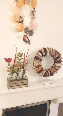 Dekoidee: Holzkranz auf Metallsockel mit frischen Blumen und einem Windspiel kombiniert.