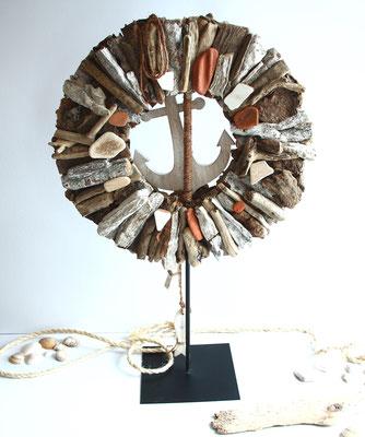 Kranz aus Treibholz auf Metallständer mit maritimer Dekoration.
