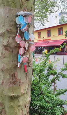 Hier hängt unser Windspiel an einem Straßenbaum im Hamburger Schanzenviertel - farblich passend zum gelb/roten Getränkemarkt.