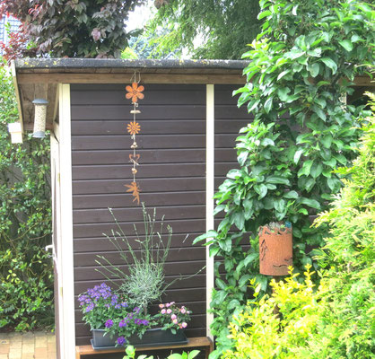 Edelrost Girlande im Garten am Gartenhäuschen dekoriert.