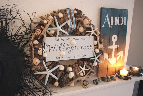 Kranz aus braunem Treibholz maritim dekoriert mit Ahoi-Holzschild, Schneckenhäusern und Teelichtern.