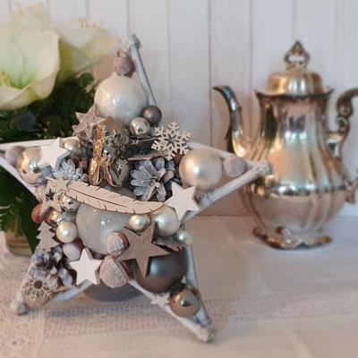 Festlicher Stern in Weiß und Silber mit silbernem Engel vor einer silbernen Kaffeekanne.