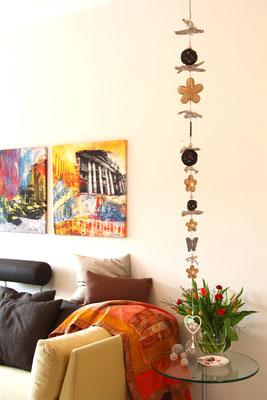 Girlande als vertikales Dekorelement in einem hohen Wohnzimmer.