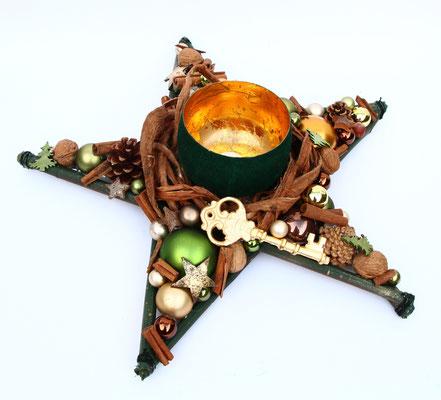 Tischdeko in Sternform mit einem goldenem Schlüssel und grünen Glaskugeln.
