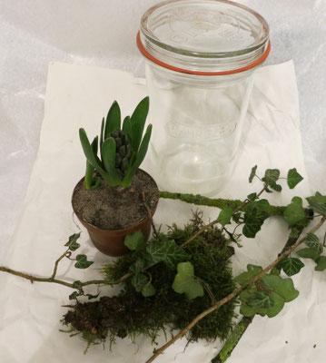 Arbeitsplatz mit Papier auslegen und das Glas und die Pflanzen draufstellen.
