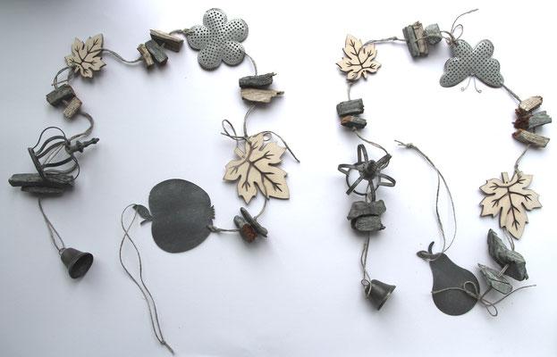 Girlanden in weiß und grau mit Metallelementen und Holzblättern.