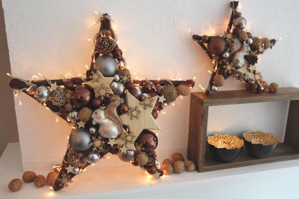 Zwei Dekosterne mit Eichhörnchen und braunen Glaskugeln verbreiten Weihnachtsatmosphäre.