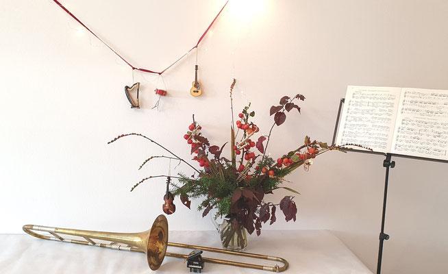 Herbststrauß mit Deko Instrumenten geschmückt. Als besondere Deko liegt eine Zugposaune vor dem Blumenstrauß.