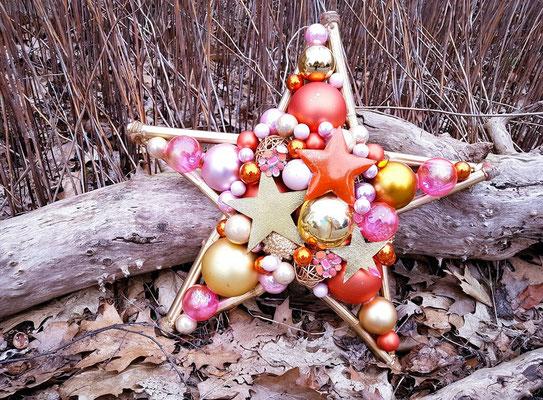 Farbenfroher und handgefertigter Deko Stern auf natürlichem Waldboden fotografiert.