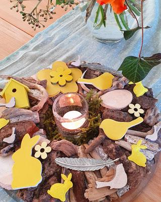 Holzkranz als Ostertisch Dekoration mit Teelicht und einem Blumenstrauß.