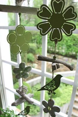 Grüne Girlande aus Metallelementen als Fensterdekor in einem Küchenfenster.
