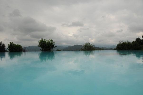 Der Pool auf dem Campingplatz mit Blick in die regenverhangenen Pyrenäen