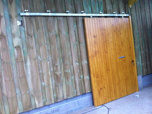 Porte de grange coulissante cadre en chêne massif et lames en sapin (Ep.27mm) finition lasure chêne clair