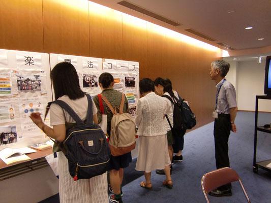 学びの内容は展示パネルで。郡司正樹先生が音楽療法コースの展示をご案内