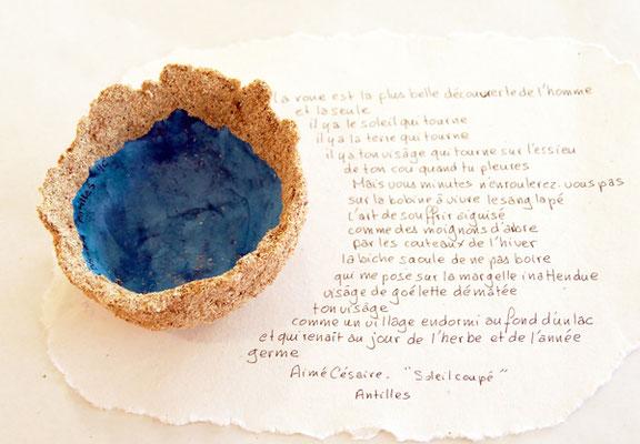 Coupe des Antilles constituée de sable et de papier avec un extrait de poème d'Aimé Césaire