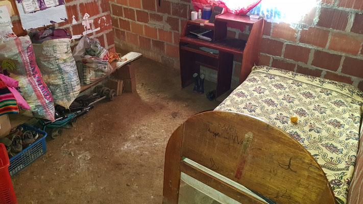 Bett und Schreibtisch der älteren Kinder. Der Fußboden besteht aus Erde.
